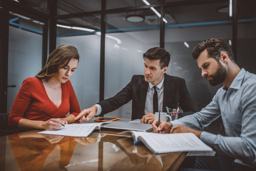 Divorced man and woman handling business and property division paperwork with their lawyer.