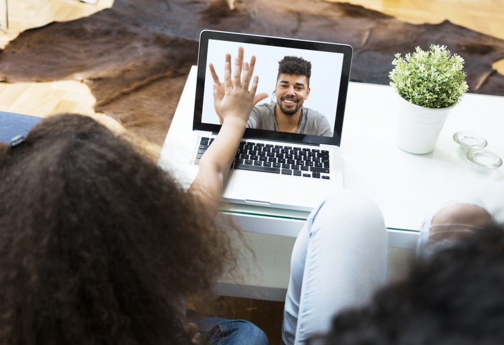 Child talking to her father on a laptop, holding hands with him on screen while the mother watches.