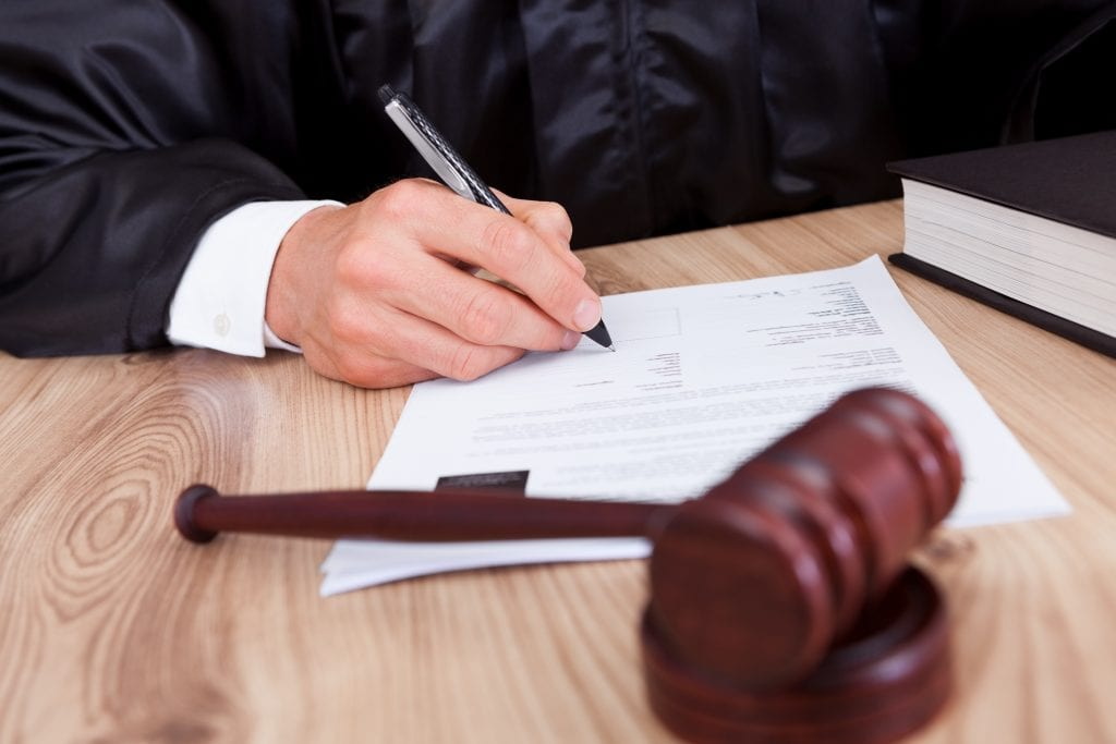 Judge signing documents with a gavel by his side.