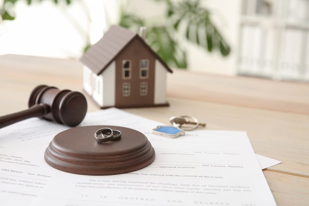 Image of law documents, gavel, a small decorative home, a house key and marriage rings.