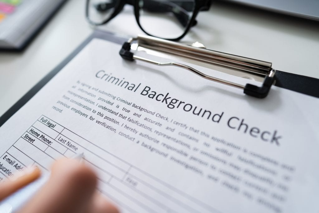 Person filling out a Criminal Background Check form.