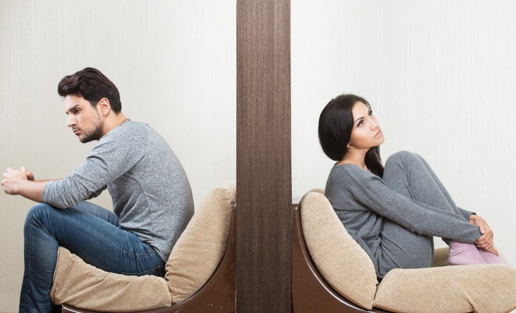 Upset man and woman sitting on opposite sides of a wall.